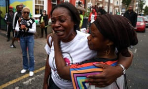 A woman is comforted outside a Kids Company premises in Camberwell, London
