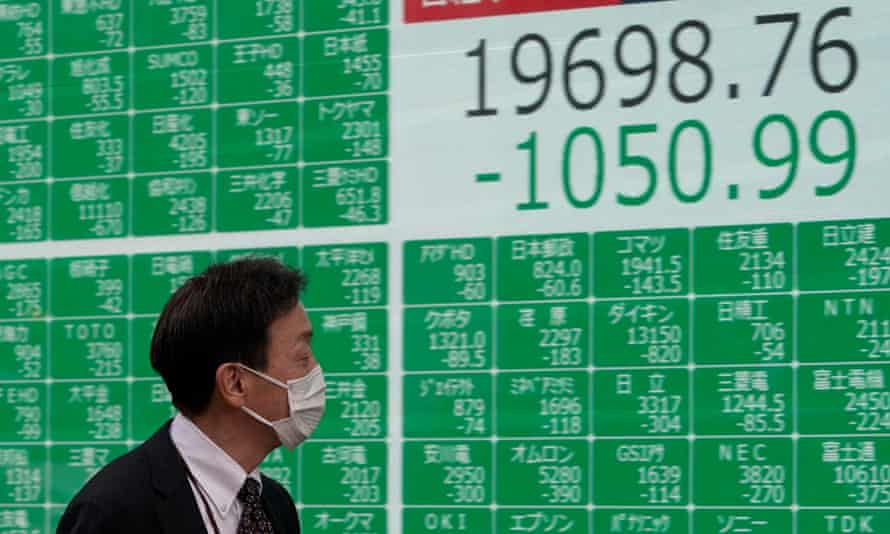 A man in a mask walks past a screen displaying information from the Tokyo stock market