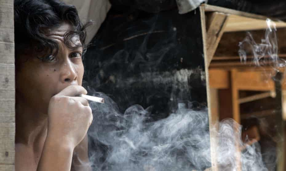 A migrant labourer from Indonesia smokes while resting in his dormitory in Kuala Lumpur