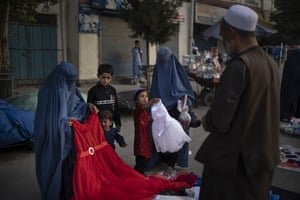 Afghan women and a girl shop for dresses at a local market in Kabul.