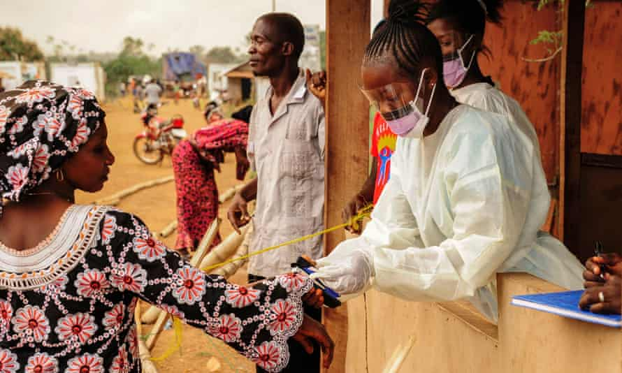 Sierra Leone health officials check passengers crossing at the border with Liberia to curb the spread of Ebola.