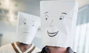 Two men wearing paper bags of happy and sad faces