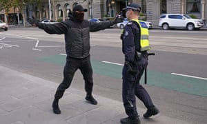 A confrontation between a man and a police officer as protesters gather outside Parliament House in Melbourne.
