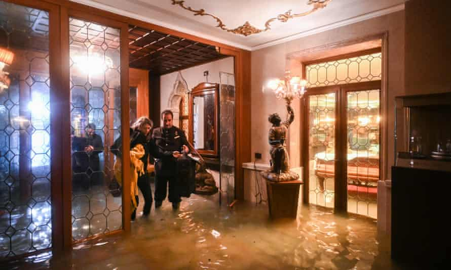 "An employee of the Gritti Palace helps a customer walk across the flooded entrance during an exceptional ""Alta Acqua"" high tide"