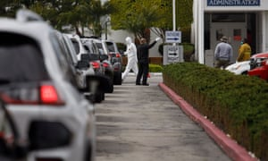 Medical personnel distribute kits at a new drive-through testing station for the coronavirus at the Crenshaw Christian Center in Los Angeles.