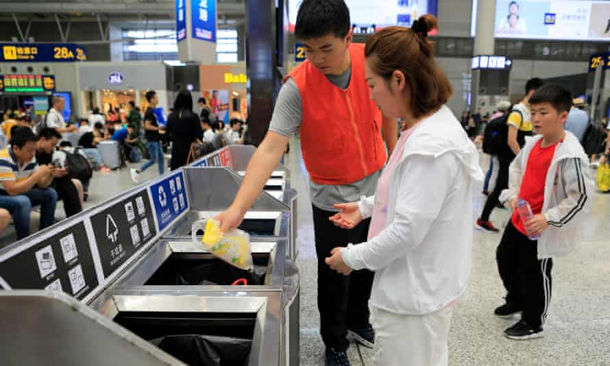 A volunteer helps a woman sort garbage in front of recycling and rubbish bins at Hongqiao railway station in Shanghai.