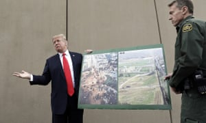 Donald Trump holds photographs of the US-Mexico border area as he reviews border wall prototypes in San Diego.