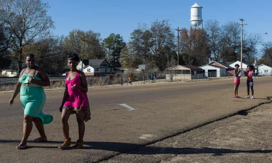 Young women walk past the site where a young man was shot dead the previous night.