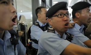 Police officers react as protesters against the Thai government scuffle with them in Hong Kong.