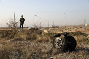 A police officer stands guard next to debris from an Ukrainian plane which was unintentionally shot down by Iran