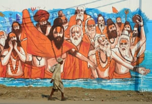 A man walks past a mural painting at Naini central jail as part of an ongoing project 'Paint my City' for the upcoming Kumbh Mela festival in Allahabad, India