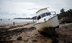 A washed up boat lies among storm debris on Wimbe beach in Pemba, Mozambique