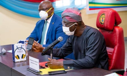 Adesola Adeduntan, left, CEO of First Bank of Nigeria, which part-funded the mobile phones, with the governor of Lagos, Babajide Sanwo-Olu.