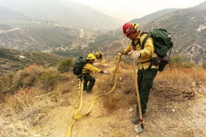 Members of the Mormon Lake Hotshots from Arizona lay hose line down rugged terrain off Highway 39 in front of the Bobcat fire.