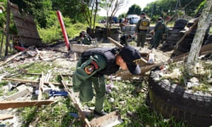 Troops inspect the site of a bomb blast in Khok Pho, Thailand.