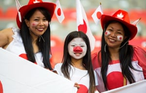 Japanese fans paint their faces and wear the host's cowgirl hats