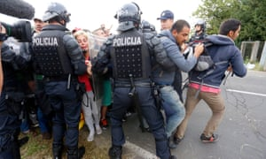 The Slovenian police allow groups of refugees to enter Slovenia through the border crossing in the Croatian village of Harmica.