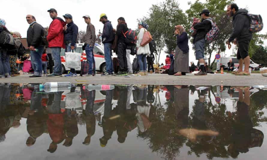 Migrants line-up to board trains at the railway station in Nickelsdorf, Austria September 5, 2015.