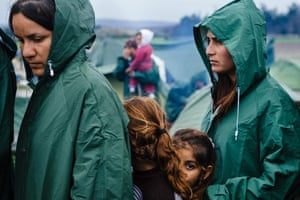 Migrants queue for food at a makeshift camp near the border between Greece and Macedonia