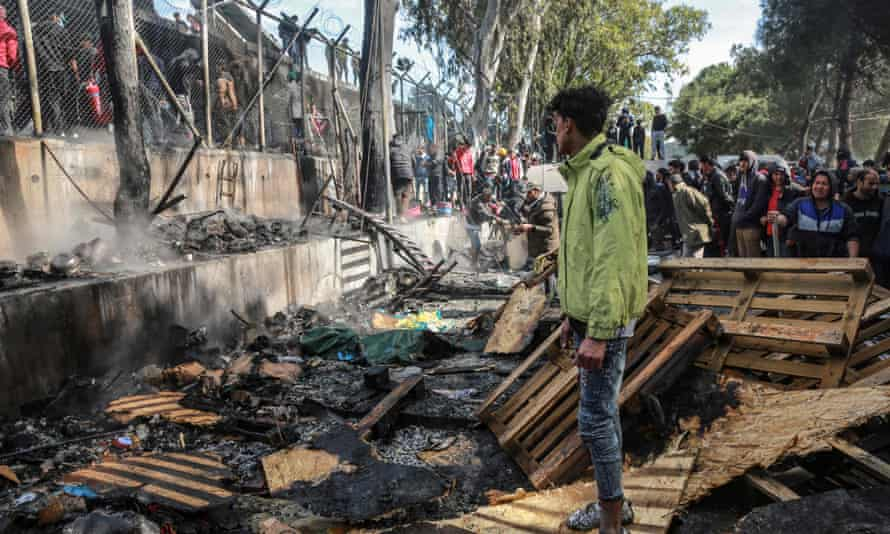Refugees and migrants stand near a burnt area after a fire broke out in Moria camp on the island of Lesbos.