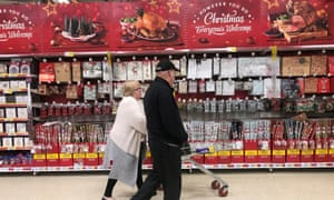 A woman pushes a shopping trolley past Christmas decorations in a Tesco store in Manchester