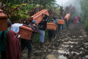 Coffins are carried that contain the remains of some of the thousands of people who were forcibly disappeared during Guatemala's brutal civil war, 1960 - 1996. Only now are they being exhumed, and identified.