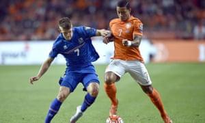 Johann Gudmundsson takes on Memphis Depay of Holland.