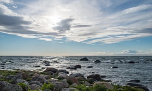 A stoney beach and shallow waters of western coast of Estonian Prangli island with beautiful cirrus clouds above.