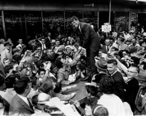 John F Kennedy stands on a platform as he shakes hands with a crowd of people that greeted him at Westview shopping center in Baltimore while campaigning for the presidency in 1960