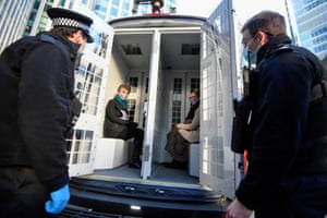 Canary Wharf, UK. Extinction Rebellion activists sit in a police car after being detained during a protest outside the Barclays offices in London