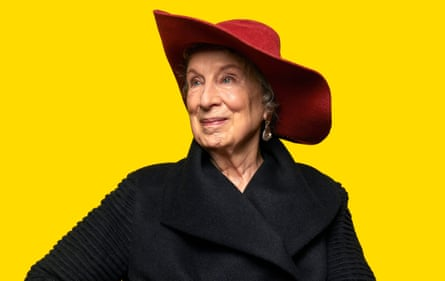 Headshot of Margaret Atwood in black coat and red hat against yellow background