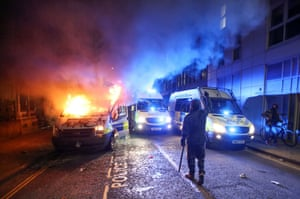 A demonstrator gestures near a burning police vehicle.