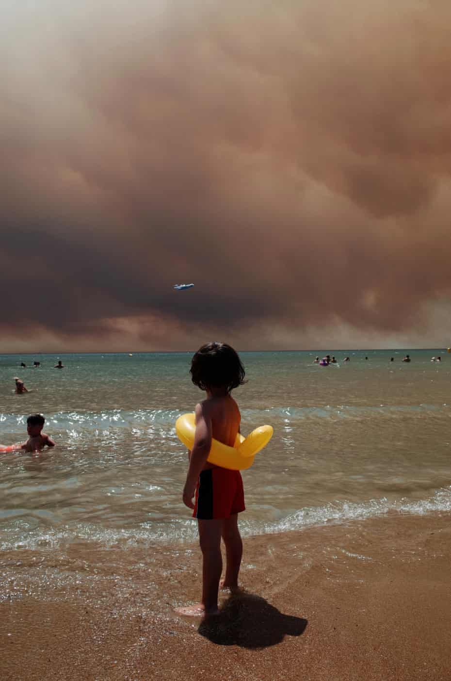 A child on a beach watches smoke from wildfires in Turkey.