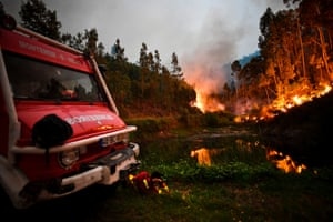 A firefighter rests next to a fire engine during a wildfire at Penela, Coimbra