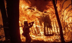 A firefighter sprays water as flames from the Camp Fire consume a home in Magalia, California in 2018