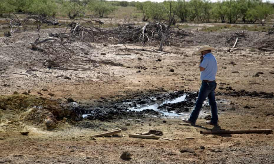 A conservation official holds his shirt over his nose as he approaches an oil-sheened pond created by an abandoned well in Pecos County.