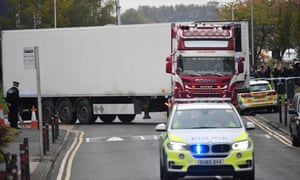 Police supervise as the lorry container in which 39 bodies were discovered is driven away from Grays.