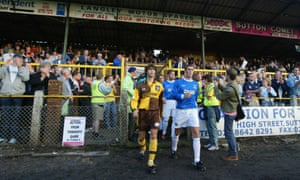 Sutton United and AFC Wimbledon players head out onto the pitch for the visitors' first ever football match.