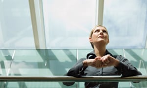 Businesswoman looking up at glass ceiling.