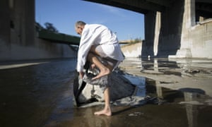 Fernando Lopez dresses after bathing in the Los Angeles river on 20 November 2015 in Los Angeles, California.