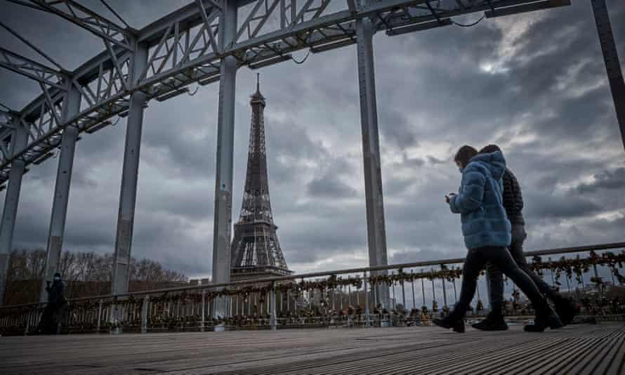 People walking passed the Eiffel tower in Paris
