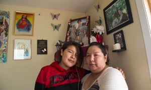 Stephanie Hookimaw, right, and her niece Karrisa Koostachin pose next to memorial photos of her daughter, Sheridan Hookimaw, who committed suicide in October.