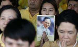 A woman in Bangkok holds a picture of Bhumibol on the 70th anniversary of his accession to the throne in June.