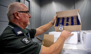 An officer of the customs authorities in the port of Rotterdam shows one of the seized boxes of vodka.
