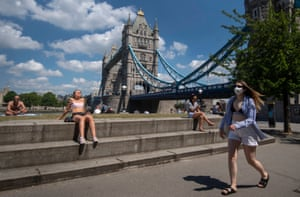 A woman in a face mask walks past people sunbathing in Potters Field, London, 21 May