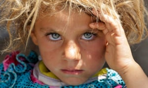 A displaced Yazidi child fleeing violence rests at the Syrian border.