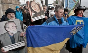Ukrainian and Tatar flags are carried along with pictures in memory of human rights activists during a 'march against hatred' in St Petersburg last month.