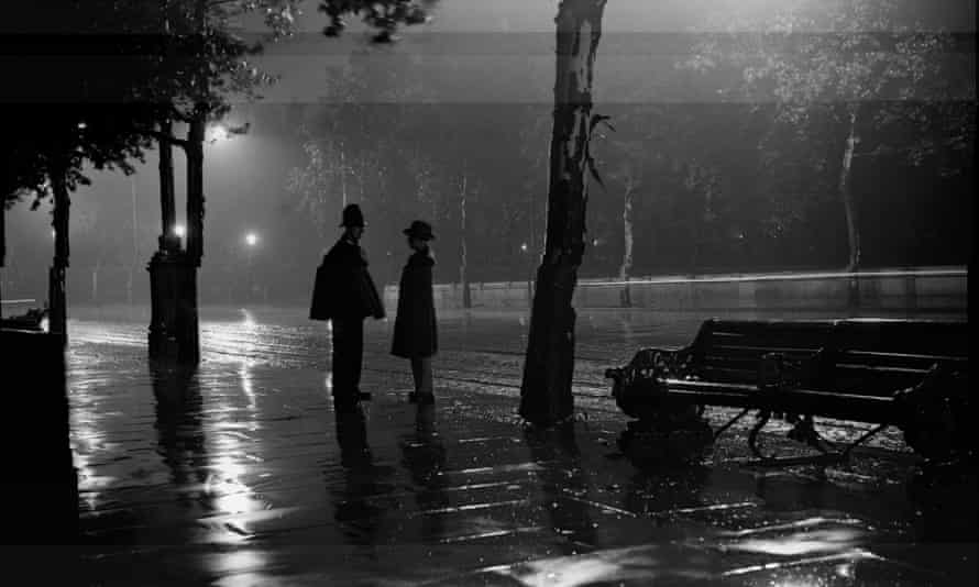 A man stops to talk to a policeman in the rain on the Thames embankment, 1929.