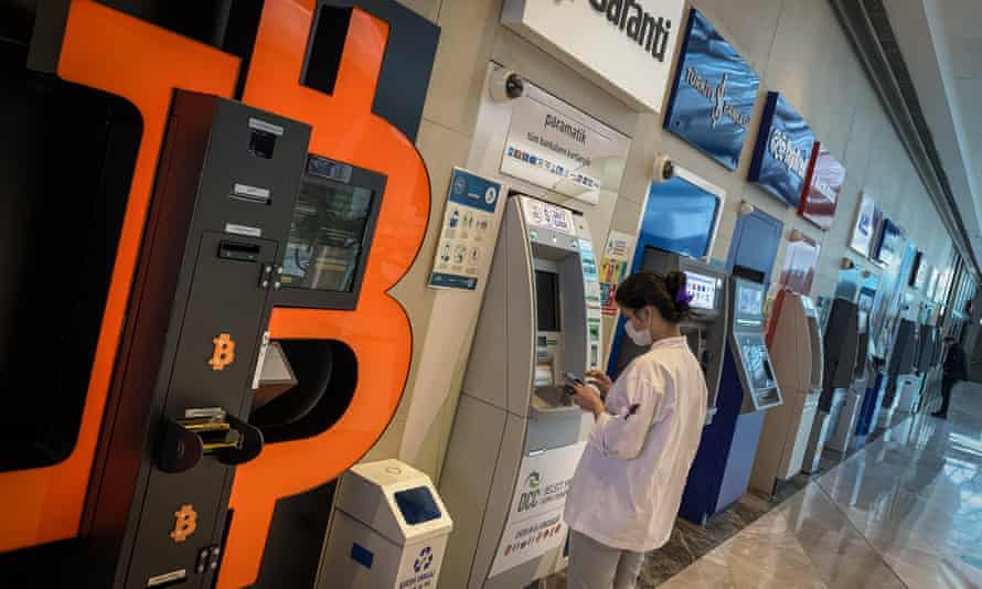 A woman uses a bank ATM next to a Bitcoin ATM machine at a shopping mall in Istanbul
