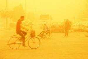 A man rides a bicycle through a sandstorm in Homs, Syria